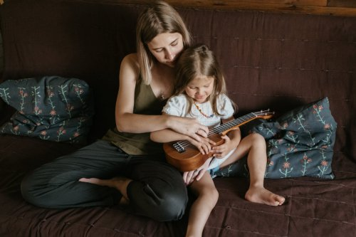 Mother with child playing ukulele
